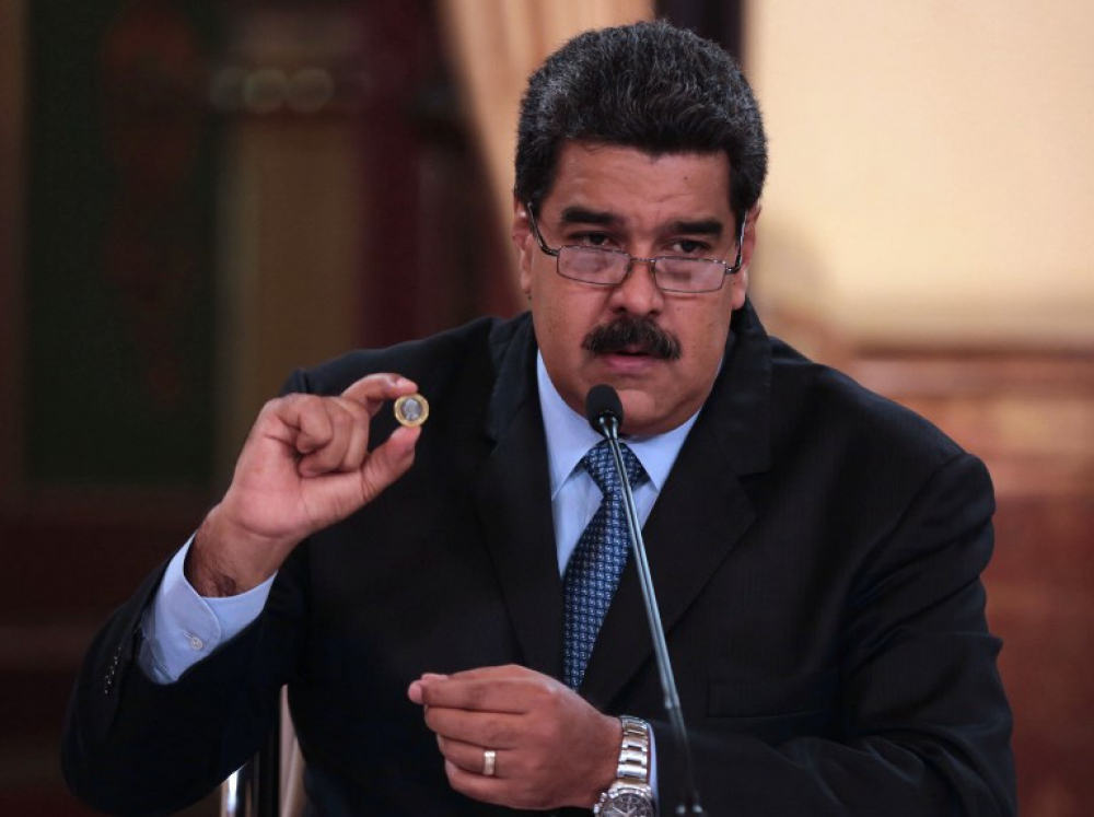 Handout picture released by the Venezuelan Presidency showing President Nicolas Maduro presenting fresh currency in the framework of new economic measures, during the broadcasting of a television programme at the Miraflores presidential palace in Caracas on August 17, 2018. Venezuela will start issuing new banknotes on Monday after slashing five zeros off the crippled bolivar -- but analysts warn the measure will do nothing to arrest a worsening economic crisis. President Nicolas Maduro has described the move as a